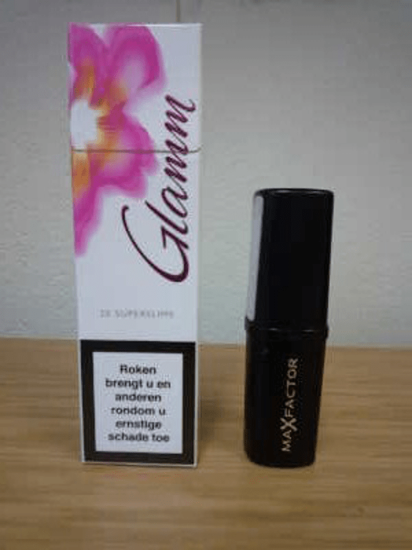 A box of cigarettes with white and pink packaging next to a lipstick.